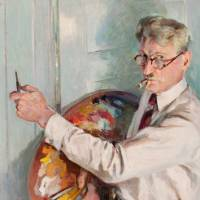 Gray-haired man wearing a white shirt and gray pants.  He is holding a palette and paintbrushes.